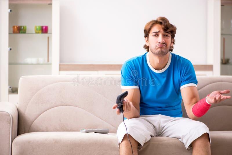 Ο νεαρός άνδρας με την τραυματισμένη συνεδρίαση βραχιόνων στον καναπέ στοκ εικόνα
