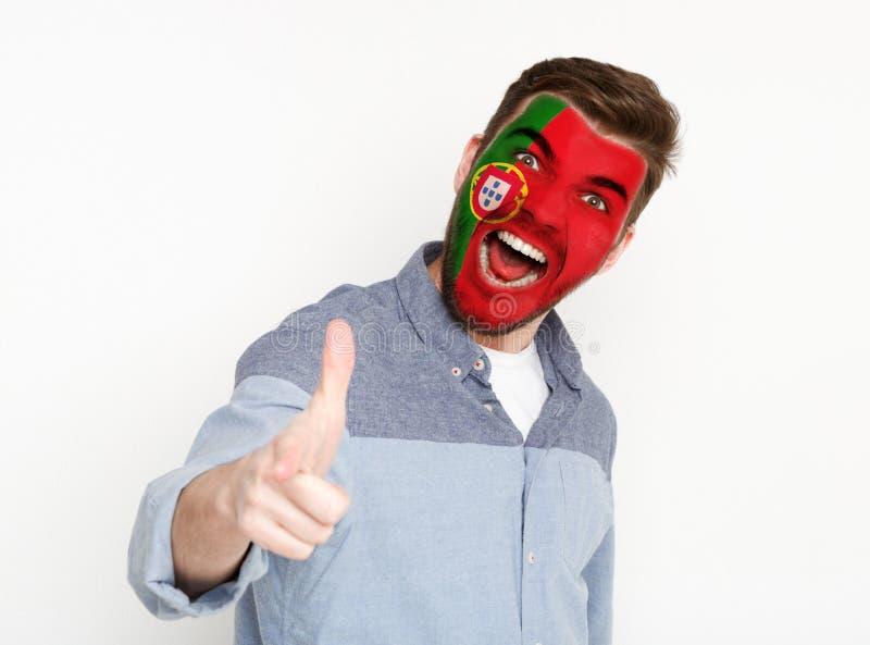 Ο νεαρός άνδρας με τη σημαία της Πορτογαλίας χρωμάτισε στο πρόσωπό του στοκ εικόνες