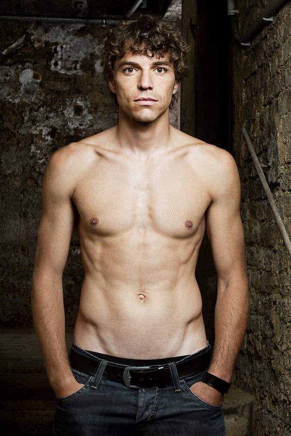 Ο νεαρός άνδρας με τους κοιλιακούς μυς στέκεται στοκ εικόνες