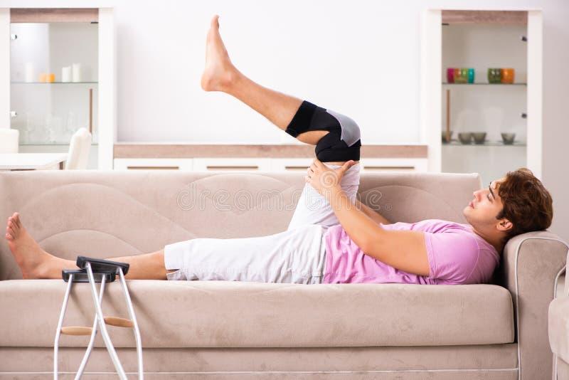 Ο νεαρός άνδρας με το τραυματισμένο γόνατο που ανακτεί στο σπίτι στοκ φωτογραφία