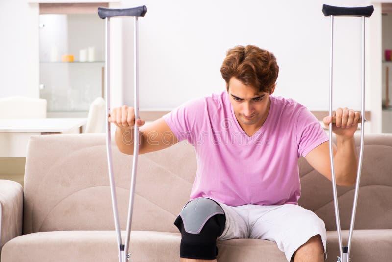 Ο νεαρός άνδρας με το τραυματισμένο γόνατο που ανακτεί στο σπίτι στοκ εικόνες