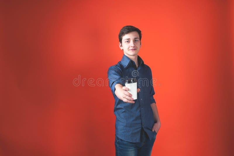 Ο νεαρός άνδρας με το φλυτζάνι εγγράφου εκμετάλλευσης με τον καφέ μέσα το χέρι και η εξέταση τη κάμερα στο υπόβαθρο κοραλλιών στοκ φωτογραφίες με δικαίωμα ελεύθερης χρήσης
