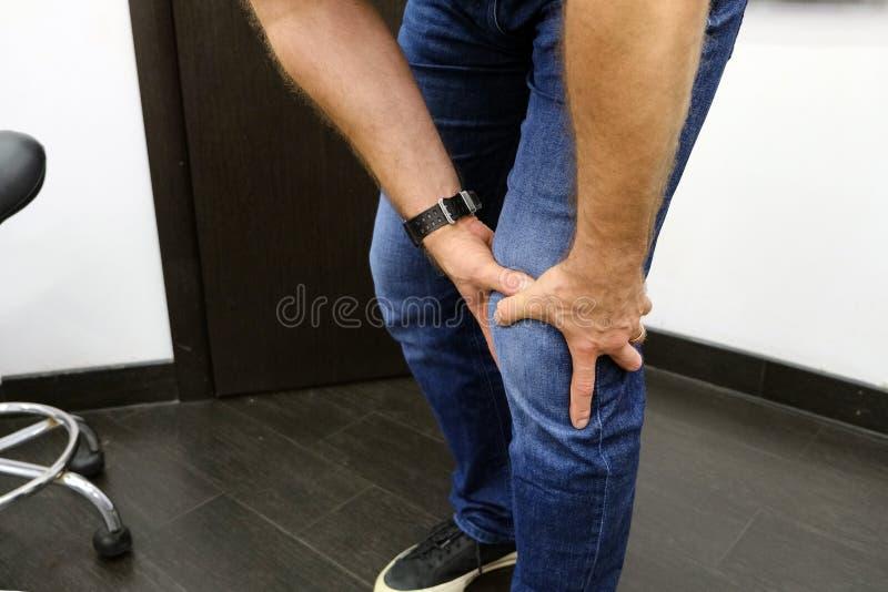 Ο νεαρός άνδρας πάσχει από τον πόνο γονάτων Αθλητικός τραυματισμός, εξάρθρωση, διάστρεμμα Άκαυστοι σύνδεσμοι γονάτων στοκ φωτογραφία με δικαίωμα ελεύθερης χρήσης