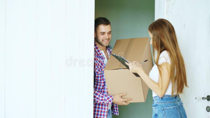Ο νεαρός άνδρας παραδίδει το κουτί από χαρτόνι στον πελάτη στο σπίτι Σημάδι γυναικών στην περιοχή αποκομμάτων για τη λήψη του δέμ στοκ εικόνες
