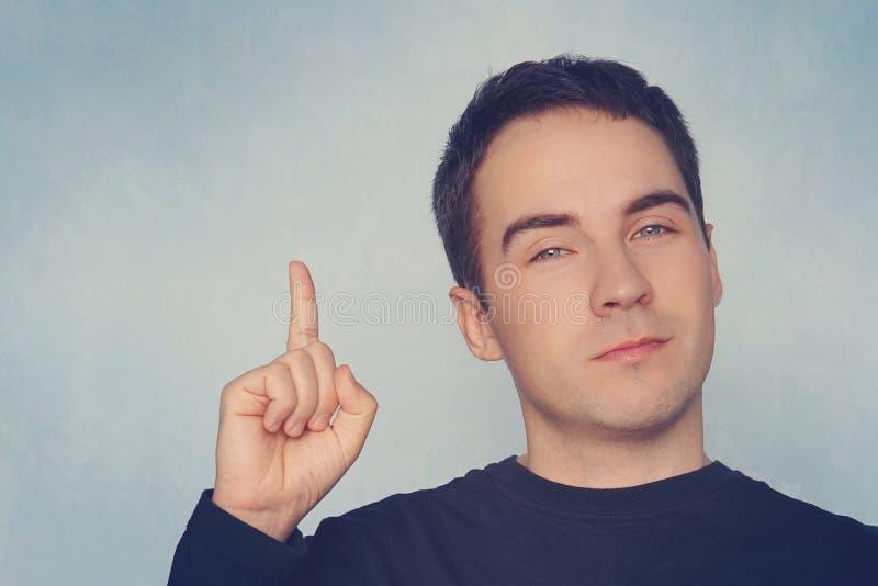 Ο νεαρός άνδρας πορτρέτου έχει μια ιδέα, που δείχνει με το δάχτυλο επάνω στο μπλε υπόβαθρο τοίχων Ο στοχαστικός τύπος έλυσε ένα π στοκ εικόνες