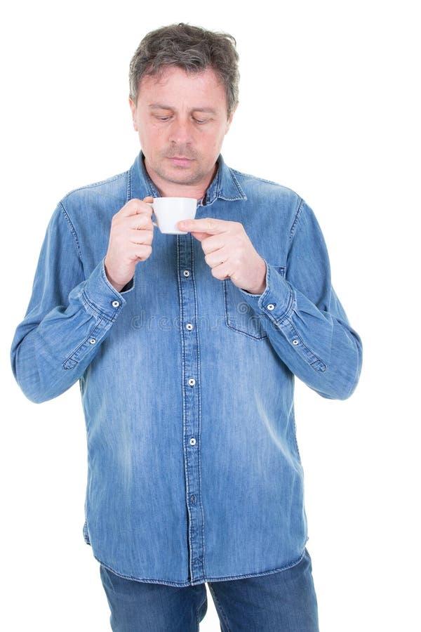Ο νεαρός άνδρας που έχει το φλιτζάνι του καφέ κοιτάζει κάτω στοκ εικόνα με δικαίωμα ελεύθερης χρήσης
