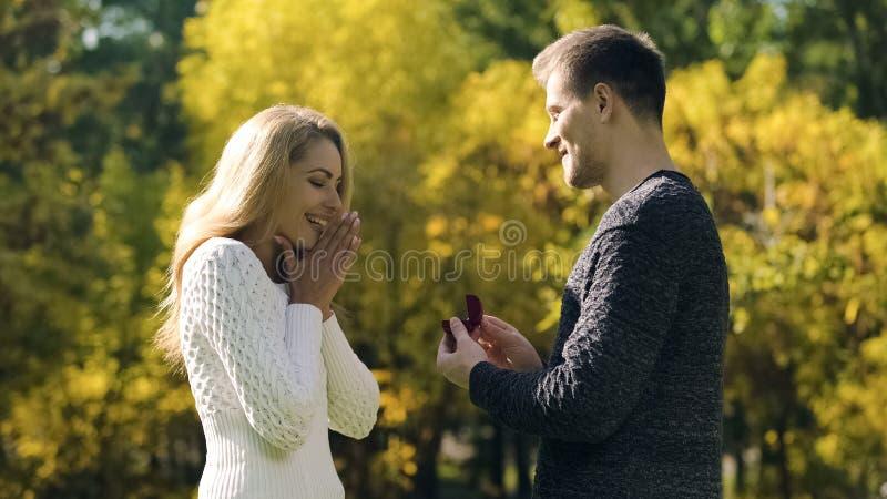 Ο νεαρός άνδρας προτείνει στη φίλη με το δαχτυλίδι, δέσμευση στο πάρκο φθινοπώρου, αγάπη στοκ φωτογραφίες