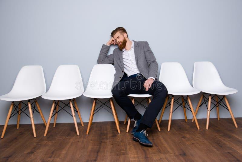 Ο νεαρός άνδρας σε formalwear με την κόκκινη συνεδρίαση γενειάδων στην καρέκλα και περιμένει στοκ φωτογραφία με δικαίωμα ελεύθερης χρήσης
