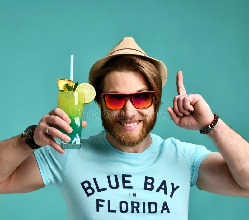 Ο νεαρός άνδρας στο καπέλο και το κόκκινο κοκτέιλ λαβής γυαλιών ηλίου πίνουν την ευτυχή κραυγή χυμού στοκ φωτογραφία με δικαίωμα ελεύθερης χρήσης