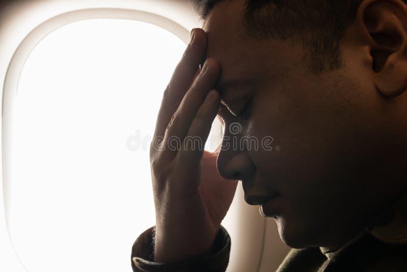 Ο νεαρός άνδρας σχετικά με το μέτωπό του με το χέρι και τα μάτια έκλεισε στο κάθισμα στο αεροπλάνο στοκ φωτογραφίες με δικαίωμα ελεύθερης χρήσης