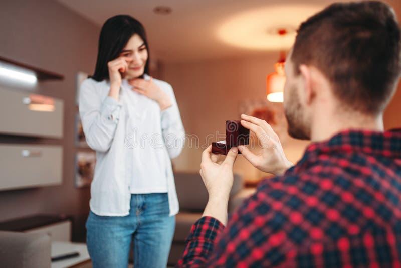Ο νεαρός άνδρας υποβάλλει μια προσφορά στην έκπληκτη γυναίκα στοκ εικόνα