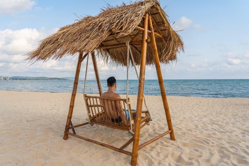 Ο νεαρός άνδρας χαλαρώνει στην ταλάντευση στην παραλία στοκ εικόνες