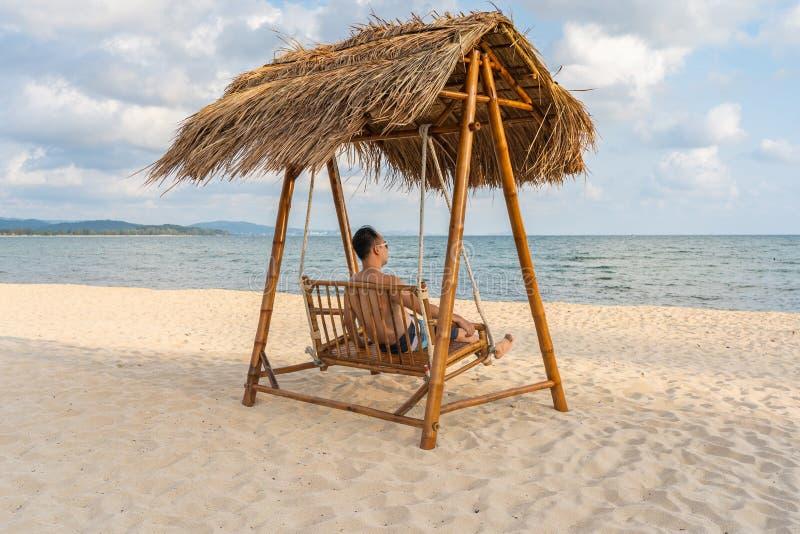 Ο νεαρός άνδρας χαλαρώνει στην ταλάντευση στις θερινές διακοπές στοκ φωτογραφία με δικαίωμα ελεύθερης χρήσης