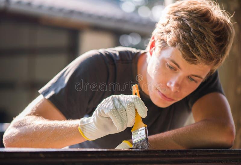 Ο νεαρός άνδρας χρωματίζει τον ξύλινο φράκτη με μια βούρτσα στοκ φωτογραφίες