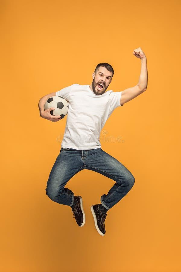 Ο νεαρός άνδρας ως ποδοσφαιριστή ποδοσφαίρου που κλωτσά τη σφαίρα στο στούντιο στοκ φωτογραφία με δικαίωμα ελεύθερης χρήσης