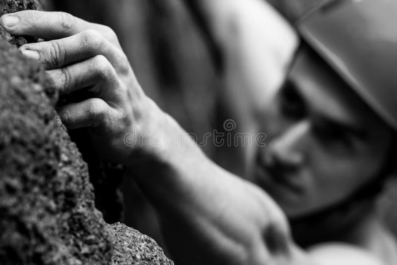 Ο νεαρός άνδρας αναρριχείται σε έναν βράχο μαύρο λευκό στοκ εικόνα