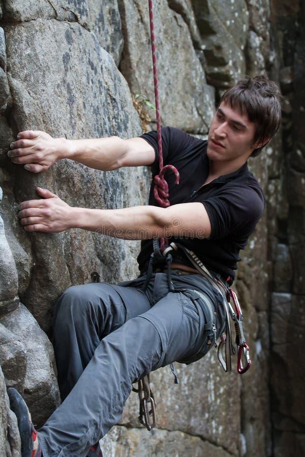 Ο νεαρός άνδρας αναρριχείται σε έναν βράχο στοκ φωτογραφίες