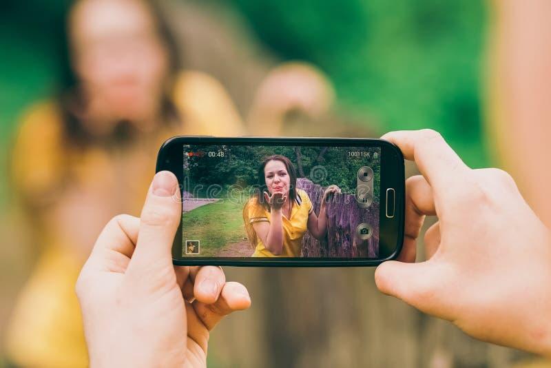 Ο νεαρός άνδρας κάνει τη φωτογραφία του φίλου κοριτσιών στοκ φωτογραφία με δικαίωμα ελεύθερης χρήσης
