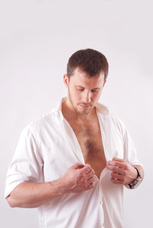 Ο νεαρός άνδρας με το όμορφο πρόσωπο, μυϊκός κορμός, έντυσε στο άσπρο ξεκουμπωμένο πουκάμισο στοκ εικόνες