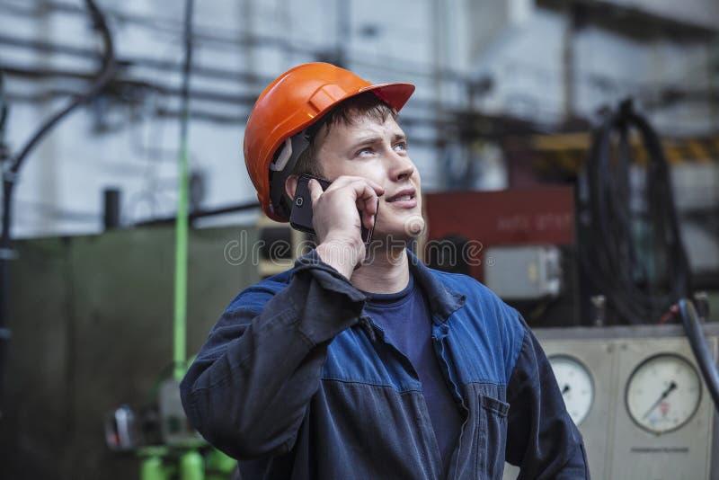 Ο νεαρός άνδρας που εργάζεται στο παλαιό εργοστάσιο στην εγκατάσταση του equi στοκ εικόνα