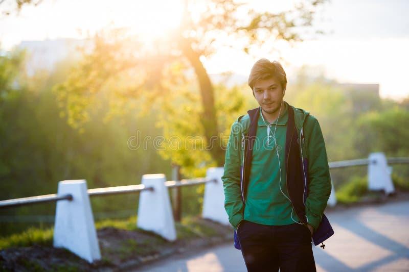 Ο νεαρός άνδρας που περπατά γύρω από την πόλη που ακούει στη μουσική με τα ακουστικά αυτιών εξετάζει τη κάμερα στο backlight και  στοκ εικόνες με δικαίωμα ελεύθερης χρήσης