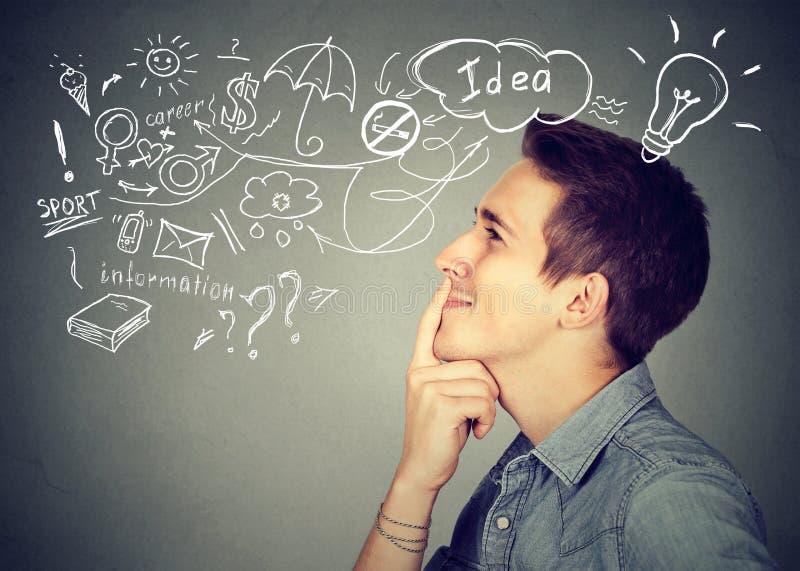 Ο νεαρός άνδρας που σκέφτεται να ονειρευτεί έχει πολλές ιδέες ανατρέχοντας στοκ εικόνα