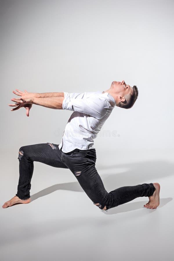 Ο νεαρός άνδρας που χορεύει σε γκρίζο στοκ φωτογραφία