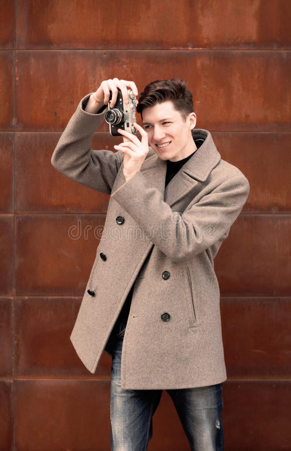 Ο νεαρός άνδρας σε ένα παλτό φωτογραφίζει το πρότυπο η εκλεκτής ποιότητας κάμερα σε έναν σκουριασμένο τοίχο μετάλλων στοκ εικόνα