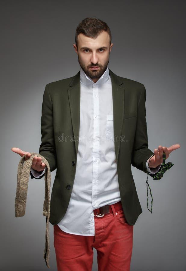 Ο νεαρός άνδρας σε ένα πράσινο κοστούμι, επιλέγει έναν δεσμό ή το δεσμό τόξων στοκ εικόνα με δικαίωμα ελεύθερης χρήσης
