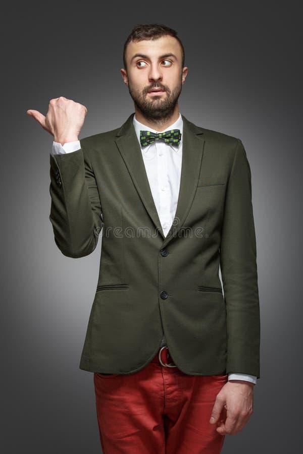 Ο νεαρός άνδρας σε ένα πράσινο κοστούμι, παρουσιάζει αριστερά στοκ εικόνες