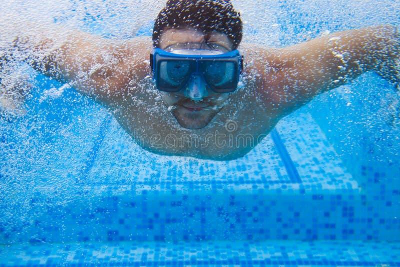 Ο νεαρός άνδρας στη μάσκα κατάδυσης που κολυμπά το μέτωπο σέρνεται σε μια λίμνη, tak στοκ εικόνες