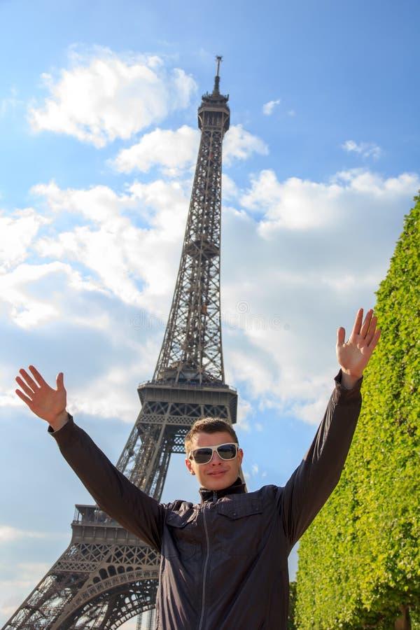 Ο νεαρός άνδρας hipster παρουσιάζει πύργο του Άιφελ, Γαλλία στοκ φωτογραφία