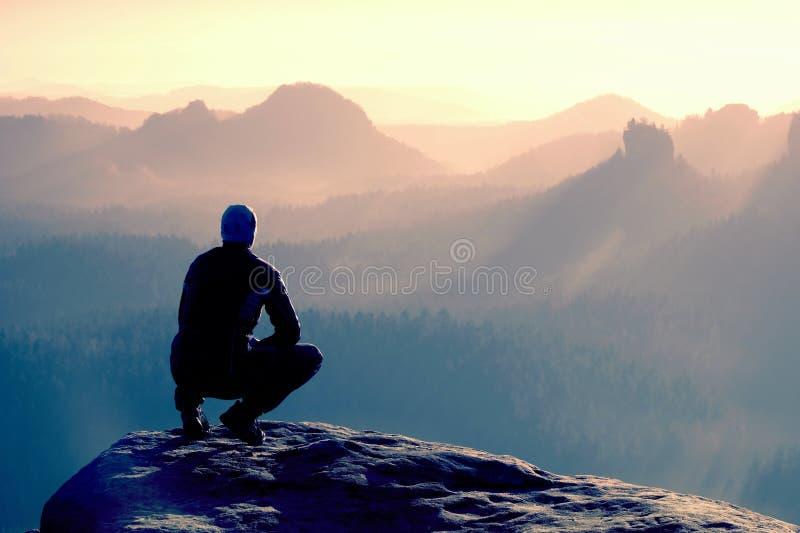 Ο νεαρός άνδρας sportswear κάθεται στο cliff& x27 άκρη του s και κοίταγμα στο misty φυσητήρα κοιλάδων στοκ εικόνες