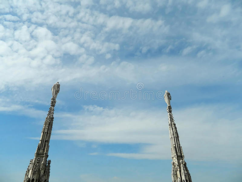 Ο νεφελώδης ουρανός πέρα από το Μιλάνο Duomo και αυτό είναι δύο κώνοι με τα αγάλματα στοκ φωτογραφίες