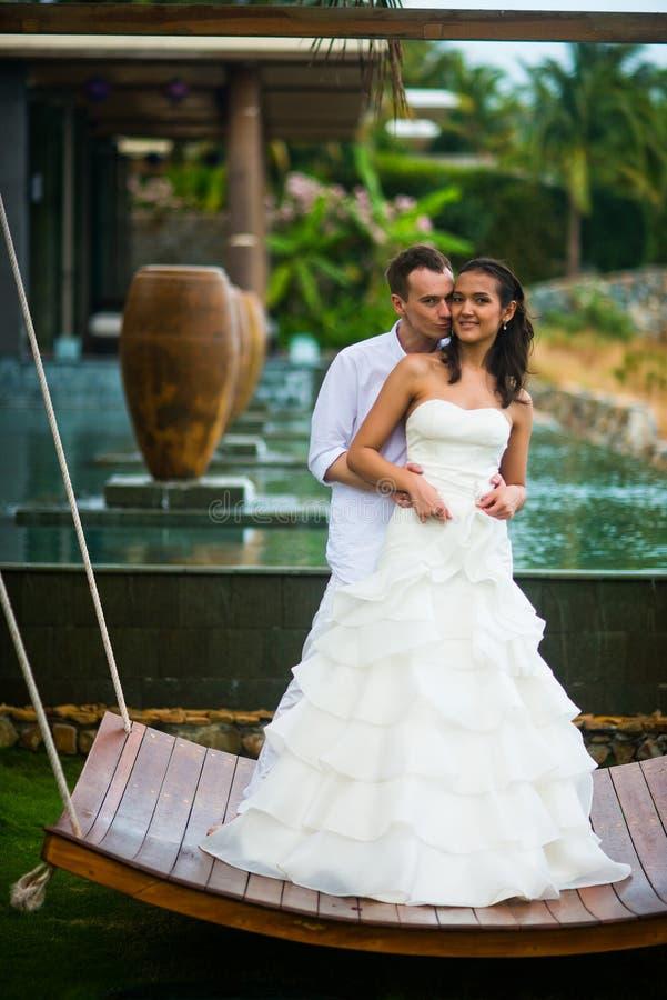 Ο νεόνυμφος αγκαλιάζει τη νύφη ενάντια στο όμορφο εσωτερικό με μια πισίνα στοκ φωτογραφίες