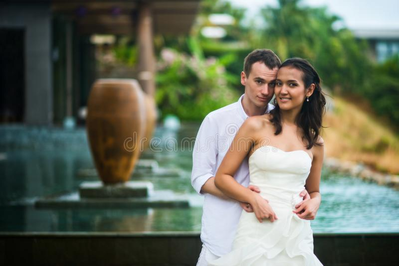 Ο νεόνυμφος αγκαλιάζει τη νύφη ενάντια στο όμορφο εσωτερικό με μια πισίνα το καλοκαίρι στοκ φωτογραφία με δικαίωμα ελεύθερης χρήσης