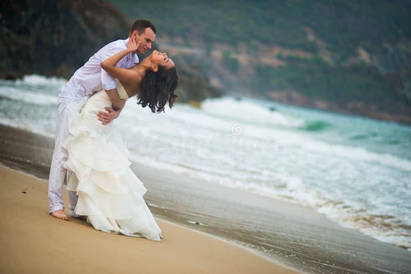 Ο νεόνυμφος αγκαλιάζει τη νύφη στη θάλασσα ζεύγος ερωτευμένο σε μια εγκαταλειμμένη παραλία στοκ εικόνες με δικαίωμα ελεύθερης χρήσης