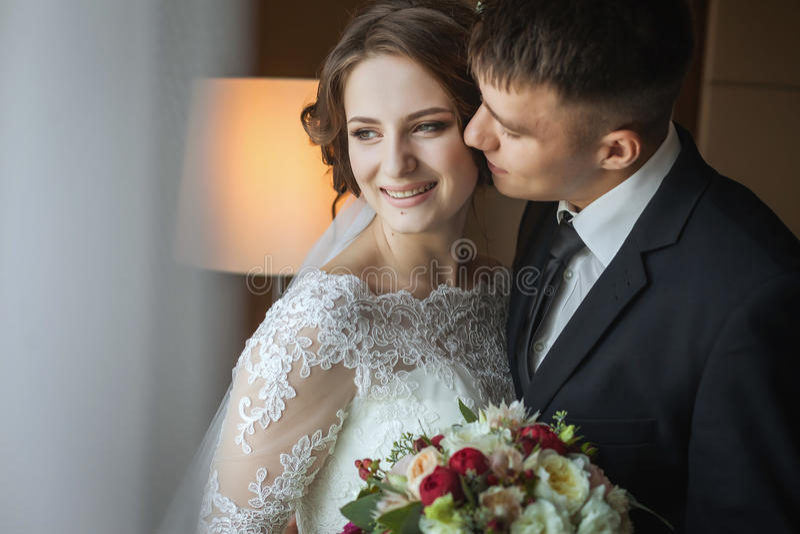 Ο νεόνυμφος αγκαλιάζει και φιλά τη νύφη στοκ φωτογραφία με δικαίωμα ελεύθερης χρήσης