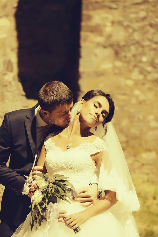 Ο νεόνυμφος κρατά και φιλά τη νύφη στοκ φωτογραφίες