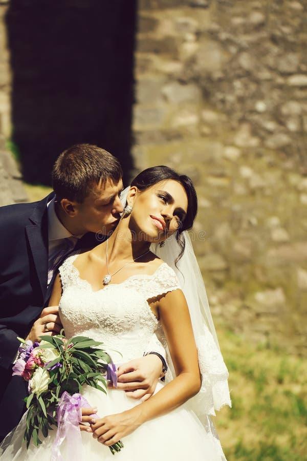 Ο νεόνυμφος κρατά και φιλά τη νύφη στοκ εικόνες
