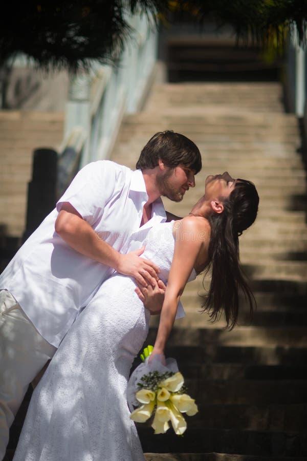 Ο νεόνυμφος κρατά τη νύφη από τη μέση και την φιλά παθιασμένα στα βήματα πετρών στοκ εικόνες