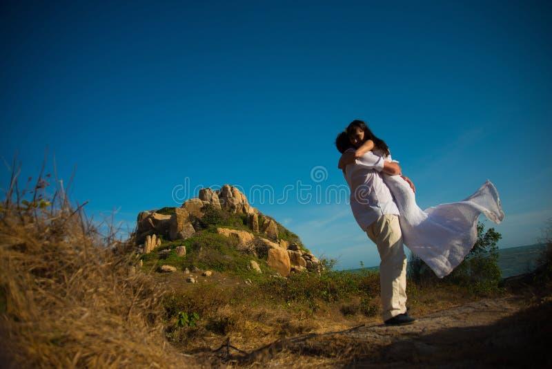 Ο νεόνυμφος κρατά τη νύφη στα χέρια του ενάντια στα βουνά και τον ουρανό στοκ εικόνα