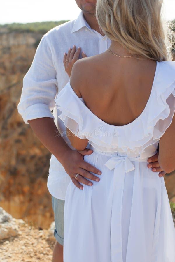 Ο νεόνυμφος που αγκαλιάζει τη νύφη στο άσπρο γαμήλιο φόρεμα στοκ φωτογραφία