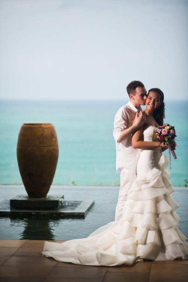 Ο νεόνυμφος φιλά μια όμορφη νύφη ενάντια στη θάλασσα στοκ εικόνες