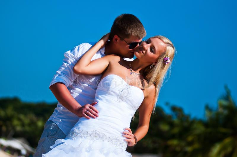 Ο νεόνυμφος φιλά τη νύφη ήπια κάτω από το μπλε ουρανό στοκ εικόνα