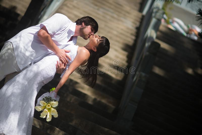 Ο νεόνυμφος φιλά τη νύφη παθιασμένα στα βήματα πετρών στοκ εικόνες