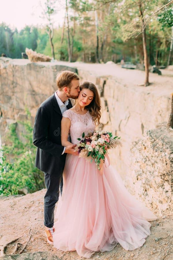 Ο νεόνυμφος φιλά τη νύφη του Ευτυχές αγκάλιασμα newlyweds Ο άνδρας στο σμόκιν και τη γυναίκα σε ένα ρόδινο γαμήλιο φόρεμα θέτει ε στοκ φωτογραφία