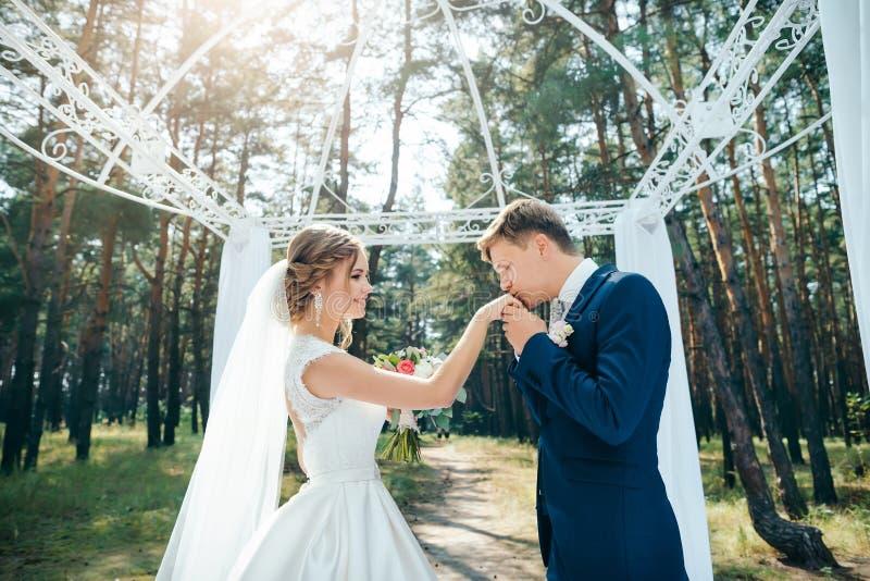Ο νεόνυμφος φιλά το χέρι νυφών ` s στη γαμήλια τελετή στοκ εικόνα