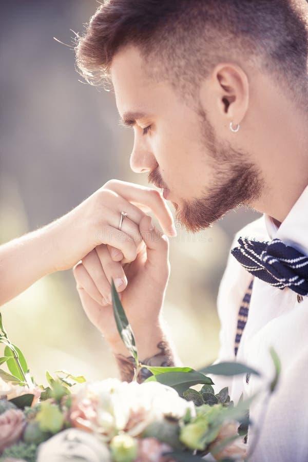 Ο νεόνυμφος φιλά το χέρι της νύφης στοκ φωτογραφίες με δικαίωμα ελεύθερης χρήσης