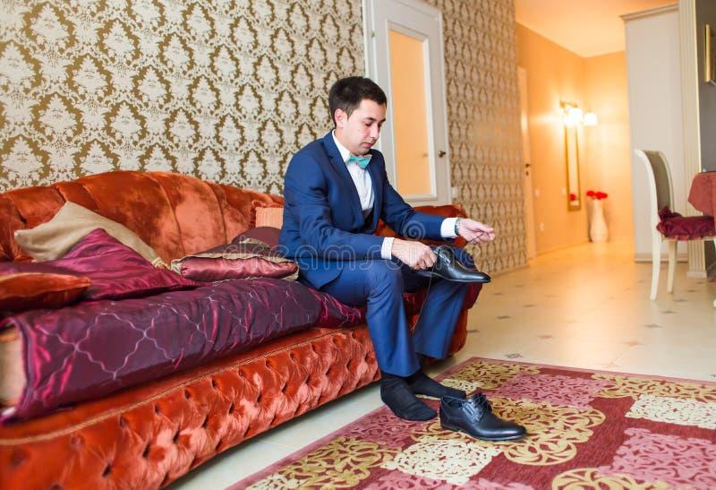 Ο νεόνυμφος φορά τα παπούτσια στο εσωτερικό Αρσενικό πορτρέτο του όμορφου τύπου Όμορφο πρότυπο αγόρι στα ζωηρόχρωμα γαμήλια ενδύμ στοκ φωτογραφία με δικαίωμα ελεύθερης χρήσης